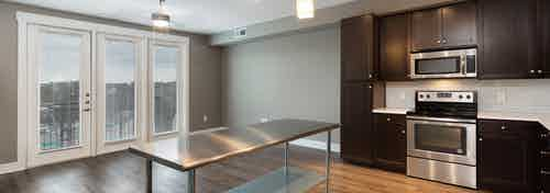 AMLI 5350 kitchen with dark wood cabinets and a white backsplash with lighter hardwood and floor to ceiling balcony doors