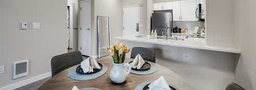 Interior view of round kitchen table set for 4 and white kitchen with stainless appliances at AMLI Bellevue Park apartments