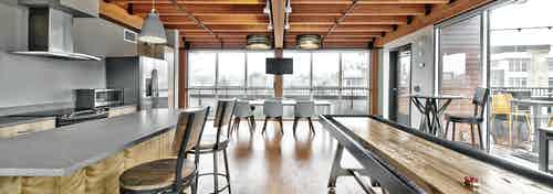 AMLI Mark 24 apartments rooftop clubroom with kitchen and shuffleboard table and table with six chairs and large windows