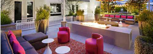 Daytime view of AMLI Lex on Orange outdoor fireplace hearth and lounge with comfortable seating, tables and grill station