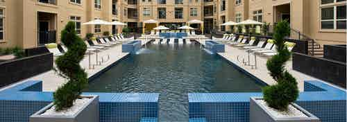 Daytime view of AMLI RidgeGate pool with blue tile cascading waterfalls onto pool and Jacuzzi sides and water ledge loungers