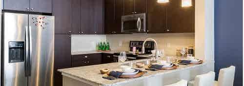 Kitchen at AMLI on Riverside with dark wood cabinets and granite countertops with creme backplash and barstools at counter