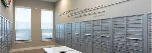 Interior of AMLI on Aldrich mailroom with grey mailboxes along neutral colored walls with light flooring and bright windows