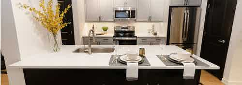 Island kitchen at AMLI Quadrangle with sleek white counters with grey cabinets and stainless steel appliances in background