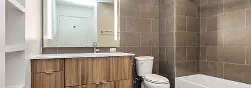 AMLI on 2nd bathroom with shower tub with large brown wall tiles and toilet with single vanity sink and built in white shelf