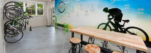 AMLI Buckhead bike storage and repair room with bikes stored vertically and a wooden table in front of a bicycle shadow mural
