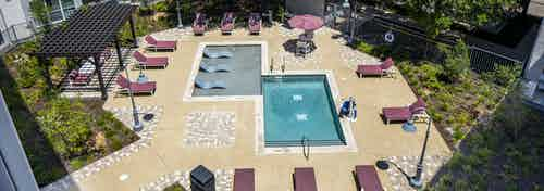 Aerial view of smaller shallow courtyard pool at AMLI South Shore apartments with burgundy lounge chairs and a wood pergola