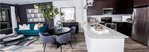 An AMLI Joya apartment contemporary living area and kitchen with stainless steel appliances and dark cabinetry