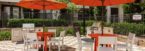 Barbecue area at AMLI on Riverside with orange tables and white chairs under umbrellas with shrubs and stainless steel grills