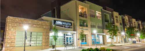 Nighttime exterior of AMLI Arista apartment building main entrance with several trees and sidewalks and brightly lit signage