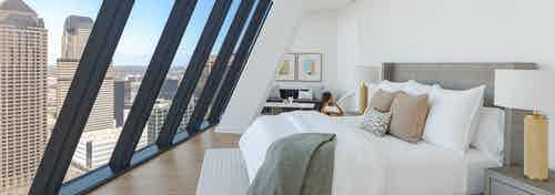 Sloped floor to ceiling windows in AMLI Fountain Place apartment with white walls and king bed with white rug on wood floor