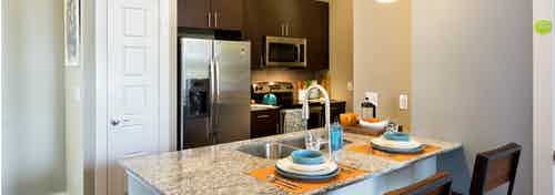 AMLI at Mueller kitchen with stools at a granite counter with dark wood cabinets and stainless steel appliances in background
