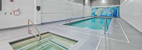 AMLI Bellevue Park indoor pool and spa with colorful mural on the back wall and light grey floors and white walls