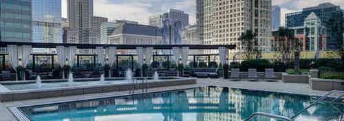 Evening view of the AMLI River North rooftop pool with surrounding lounge chairs and the Chicago skyline visible in the back