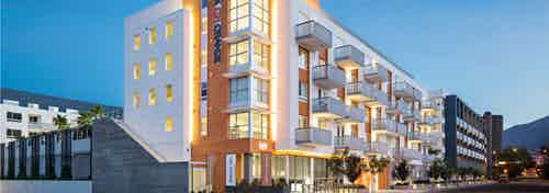 Exterior orange, white and blue rendering of AMLI Lex on Orange apartment building lit up at dusk and trees on empty sidewalk