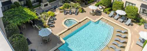 Aerial view of AMLI Las Colinas apartments courtyard pool and heated spa surrounded by lounge chairs and a grilling station
