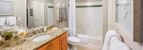 Interior view of AMLI North Point bathroom with a large granite vanity sink next to a toilet and a white tiled bathtub