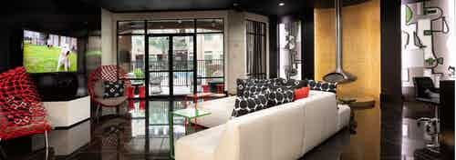 Resident lounge at AMLI Uptown apartments with white leather couch, red chairs and large TV and glass doors to pool area