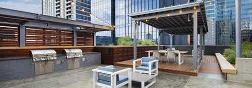 Outdoor grill area at AMLI on 2ND apartment building with two steel grills and a dining area shaded by a gray metal cabana