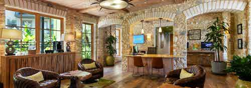 AMLI 300 leasing office with brick walls, a ceiling fan, wood-style flooring, brown leather lounge chairs, and plants