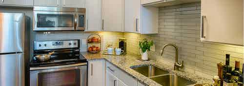 A kitchen at AMLI Denargo Market apartments with a tile back splash with white cupboards and an oven with overhead microwave
