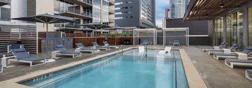 AMLI on 2ND apartments skye deck pool with gray lounge seating and gray umbrellas for shade and view of buildings