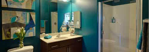 An AMLI 900 bathroom with geometric canvases hanging on teal walls featuring a white toilet, bathtub and dark wood vanity