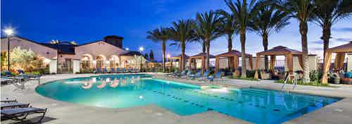 Nighttime close-up view of AMLI Spanish Hills apartment swimming pool area with lounge seating, five cabanas and palm trees