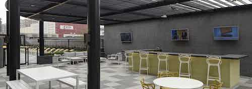 Daytime view of the grill area with available barstool and table seating options at the AMLI Lofts apartment community