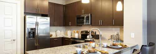 Interior of AMLI Campion Trail apartment kitchen with dark cabinets and granite countertops and stainless steel appliances
