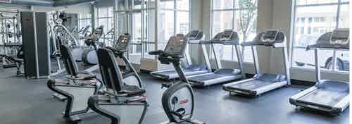 Fitness center at AMLI Arista apartments with multiple treadmills and stationary bicycles with several mirrors and windows