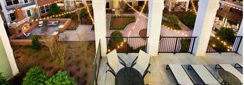 AMLI North Point terrace with a fenced in lounge area with white pillars overlooking the pristine courtyard at nighttime