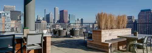 A spacious rooftop sundeck at AMLI 900 apartments with various seating arrangements and a sunny panoramic view of Chicago