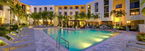 One of two swimming pools at AMLI 8800 at dusk surrounded by lush palm trees lit up, lounge chairs and building exterior