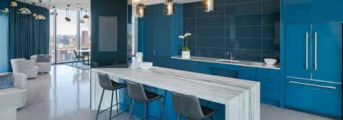 Sky lounge at AMLI Fountain Place apartments with white and grey counter and blue cabinets and dozens of hanging lights