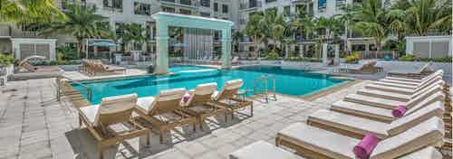 Daytime view of the AMLI Joya swimming pool with cascading fountain in the middle and modern pool loungers
