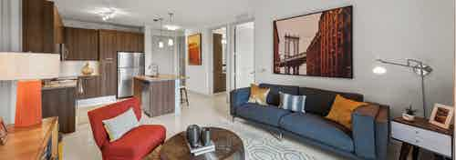 An apartment living room at AMLI 8800 with vibrant orange and blue contemporary style furniture open floorplan with kitchen