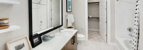 AMLI Lenox apartment bathroom with mirror over dark wood vanity with light countertop and large garden tub and walk in closet
