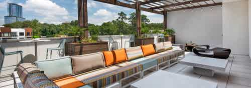 Long outdoor sofa with orange, tan and mint cushions under a pergola on the AMLI Buckhead skydeck with a bright daytime view