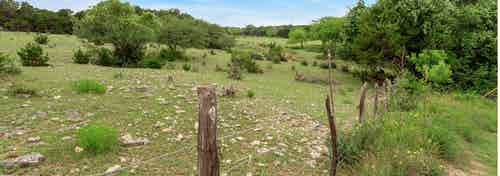Daytime view from AMLI Covered Bridge of Austin Hill Country with lush green grass, shrubbery and mature trees