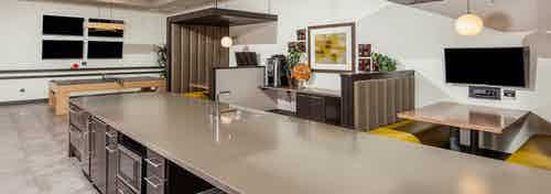 Interior view of the cyber cafe at AMLI Cherry Creek apartments showcasing a large counter top with sink and television
