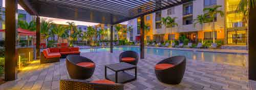 Outdoor vibrant orange seating area at AMLI 8800 with table and chairs poolside under pergola at dusk