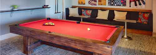 Interior view of the billiards table area at AMLI Denargo Market apartments featuring red felt on the table and wall art work