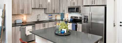 Interior view of AMLI Decatur apartment kitchen with spacious island and stainless steel appliances with a neutral backsplash