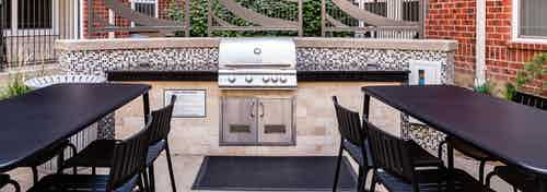 A barbecue area at AMLI Park Avenue apartments with a large surrounding counter top area and two black tables with chairs