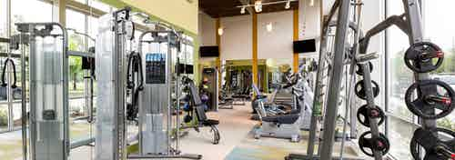Interior view of fitness center at AMLI at Mueller featuring a variety of weight machines and floor to ceiling windows