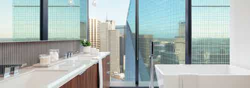 AMLI Fountain Place apartment bathroom with free standing soaking tub and a double vanity sink with views of city buildings