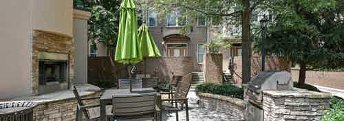 AMLI Lindbergh outdoor grilling area with fireplace and table and chairs with a green umbrella and stainless steel grill