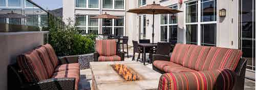 A rooftop fire pit at AMLI Park Avenue apartments with surrounding couches and tables and umbrellas and lush green plants