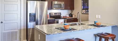 AMLI Covered Bridge gourmet kitchen with light walls, stainless steel appliances and under mount extra deep stainless sink